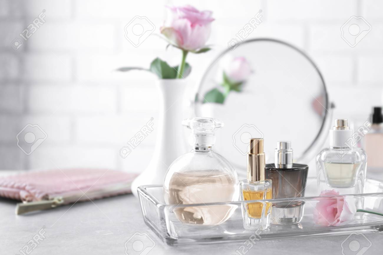 Glass tray with bottles of perfume on table - 97754603