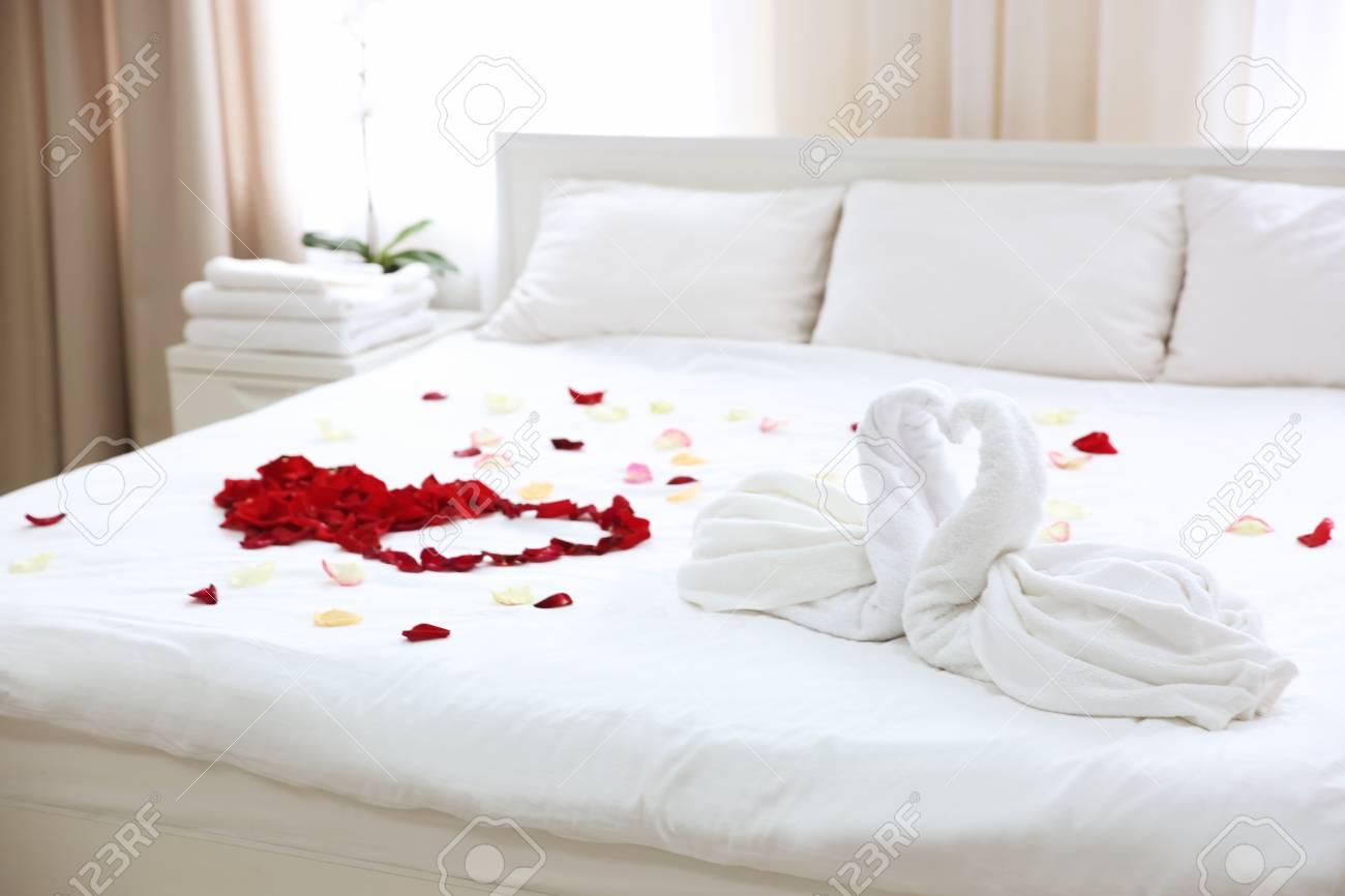 Two Towel Swans And Rose Petals On Bed In Light Hotel Room Stock Photo Picture And Royalty Free Image Image 98048287