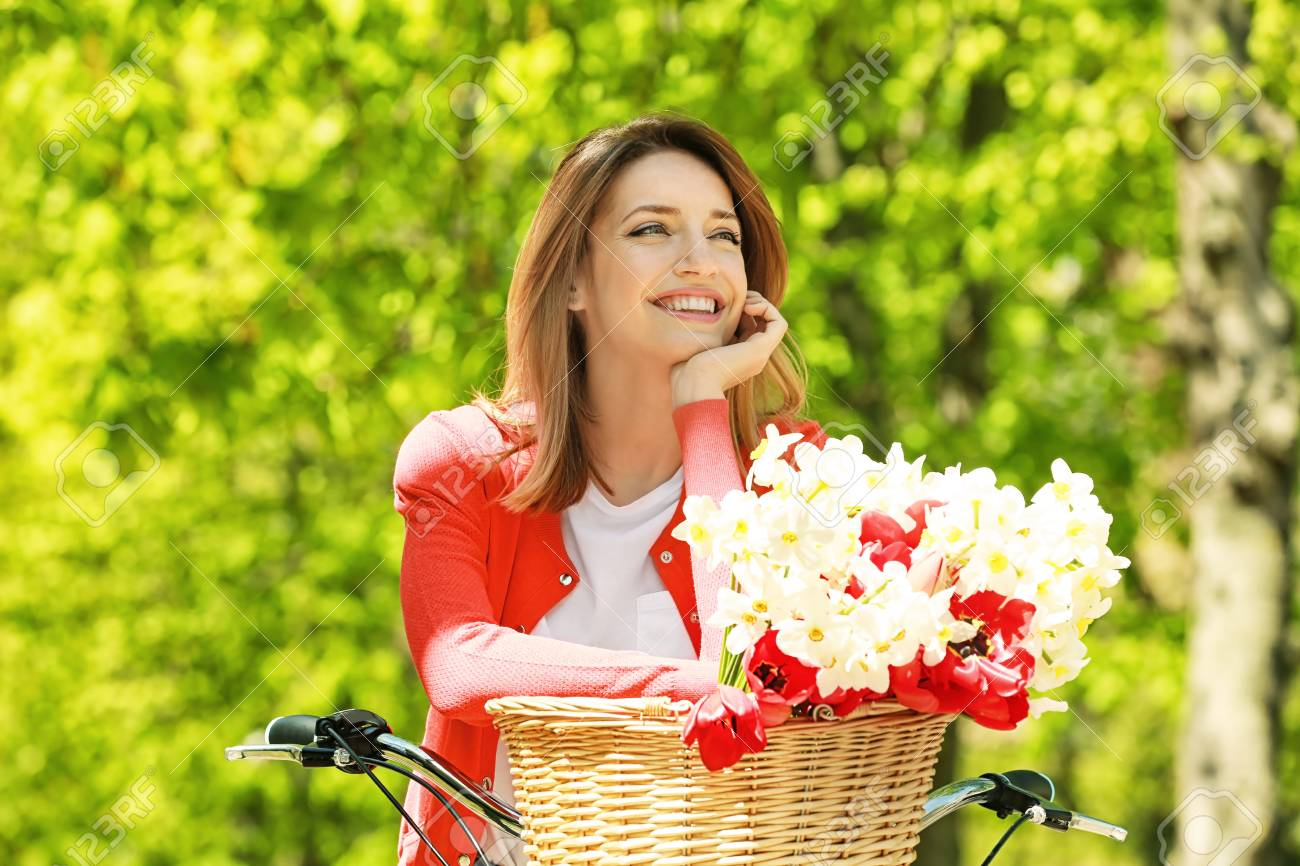 Young Beautiful Girl And Bicycle With Flowers In Basket At Park