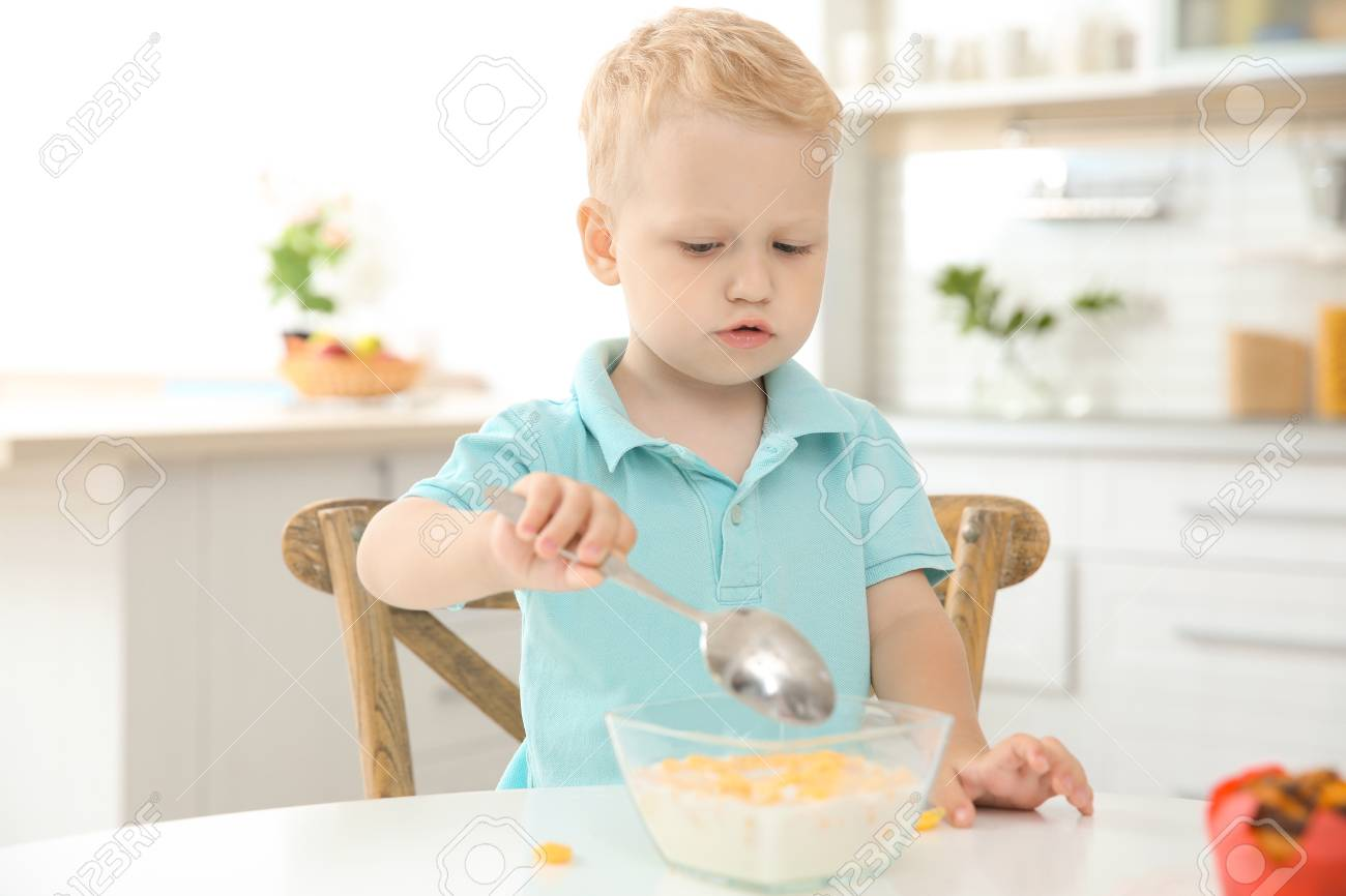 Adorable Little Boy Eating Cereal With Big Spoon In Kitchen Stock ...