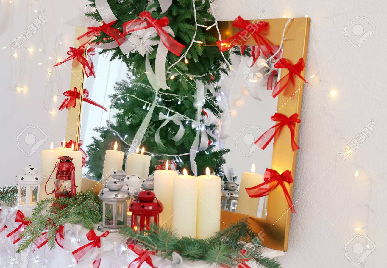 candles and christmas decorations on mantelpiece in room stock photo 98189761