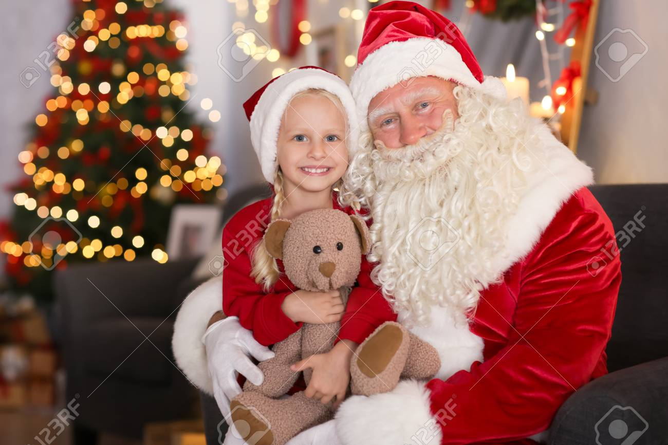4f29e7be7 Santa Claus and cute little girl with toy in room decorated for Christmas  Stock Photo -