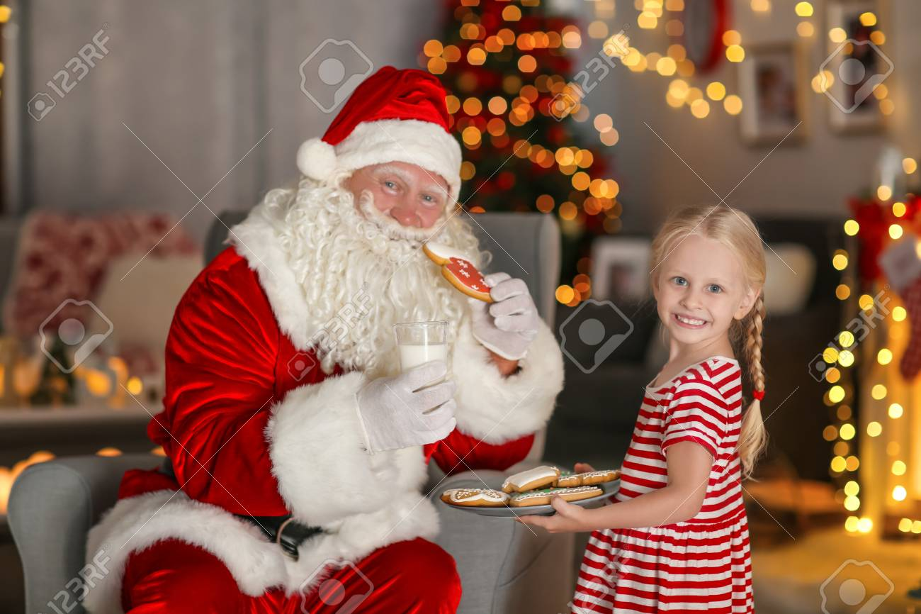 Little Girl Treating Santa With Tasty Cookies And Milk In Room