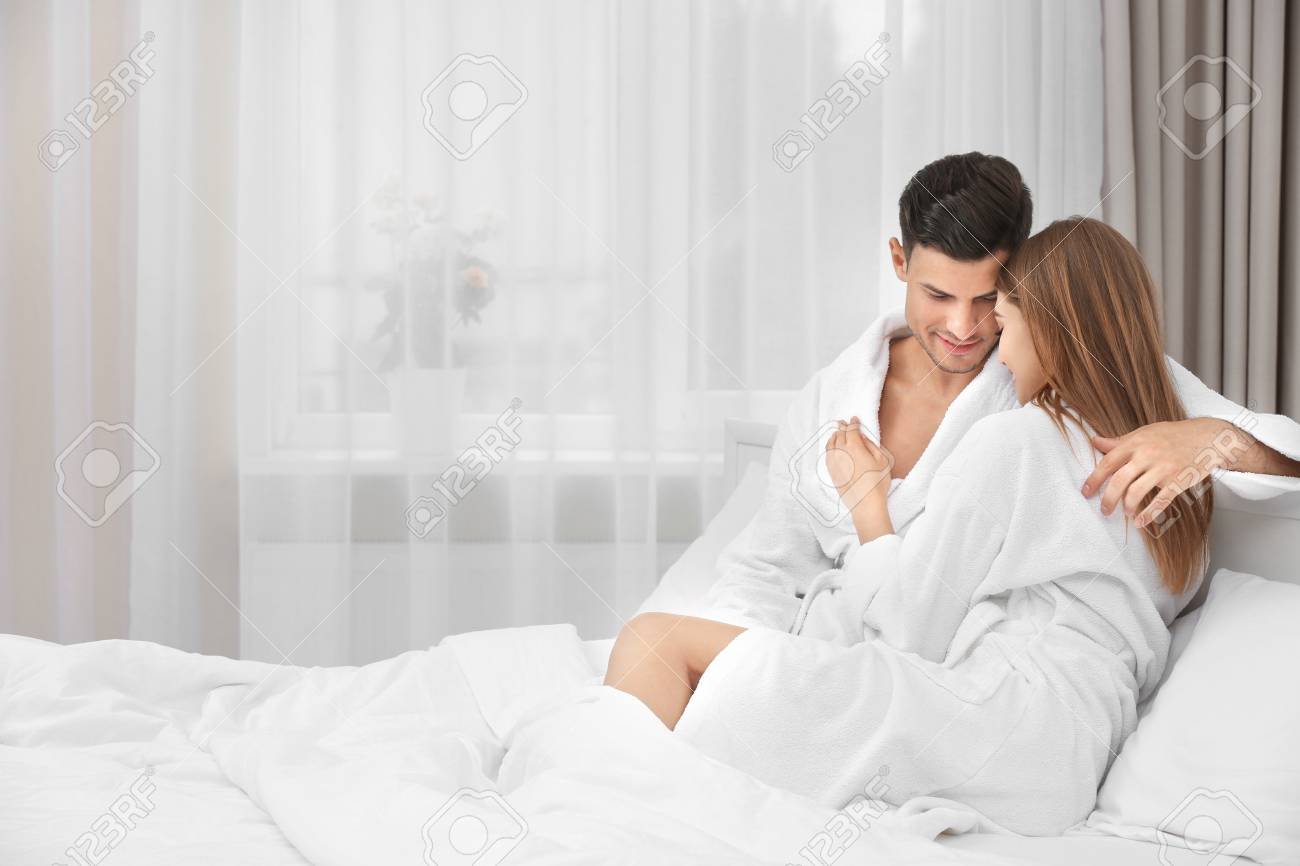 Young loving couple in bathrobes relaxing on bed at hotel Stock Photo -  98721489 4f1377416