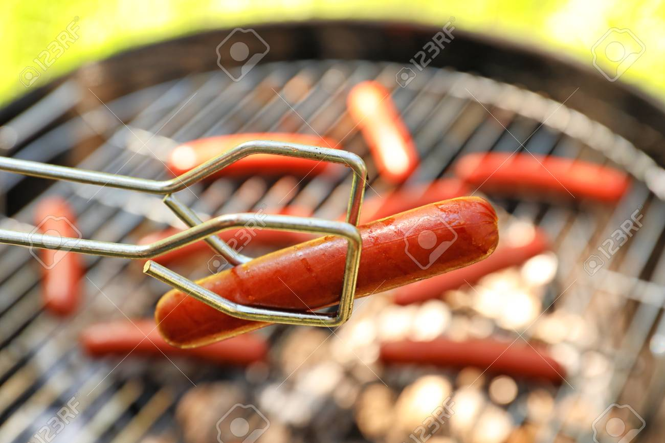 Tongs holding sausage near barbecue grill - 98584624