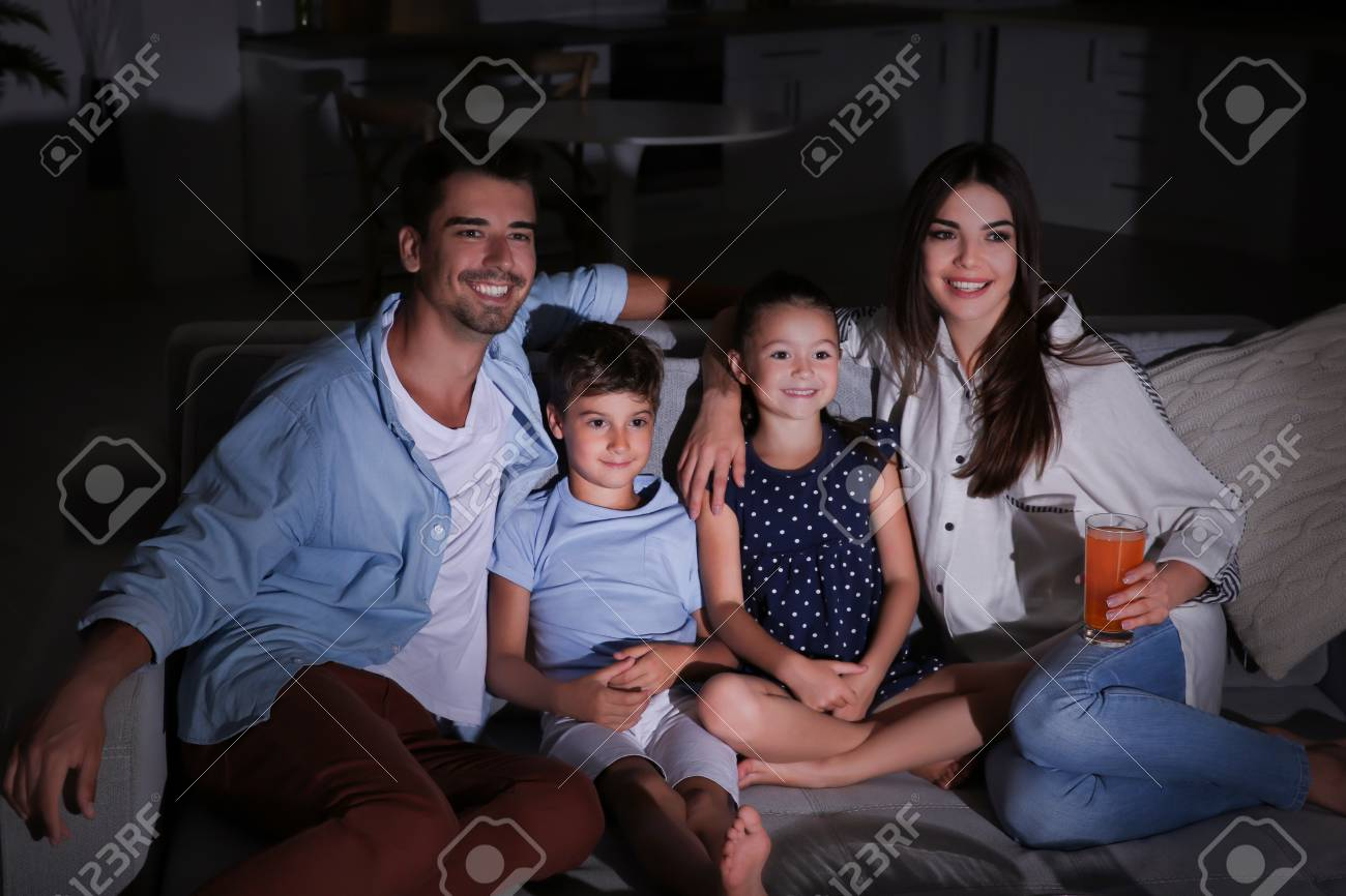 Happy family watching TV on sofa at night - 101882453