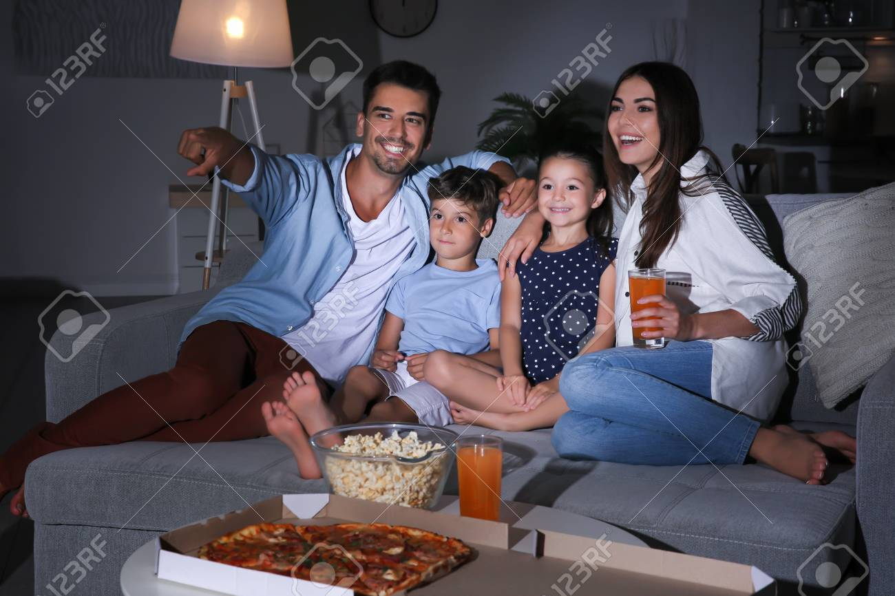 Happy family watching TV on sofa at night - 101882485
