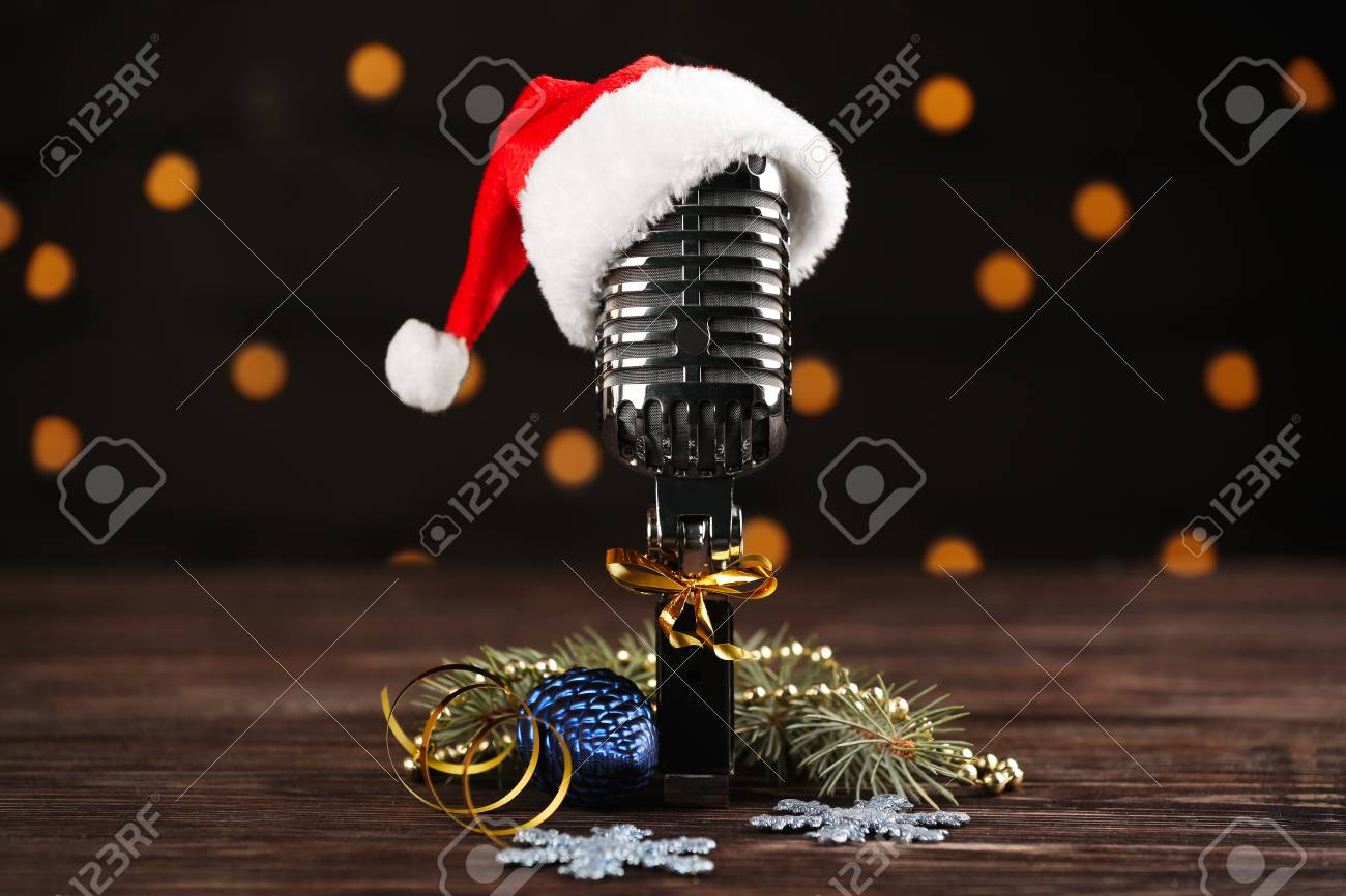 c6bc3f6d0748e Christmas music concept. Microphone with hat and decoration on wooden table  Stock Photo - 98639961