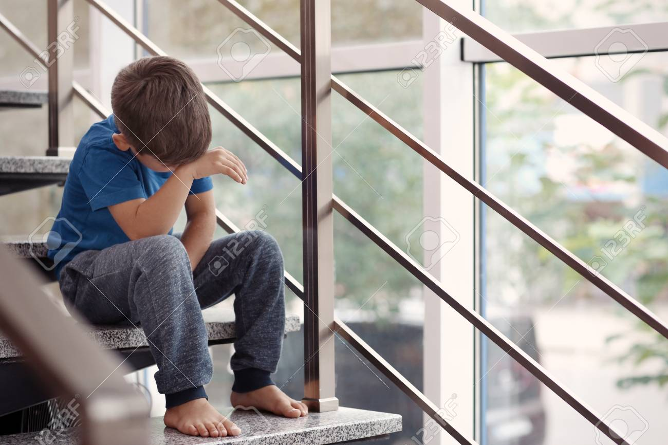 Little boy crying on stairs indoors. Domestic violence concept - 101453754