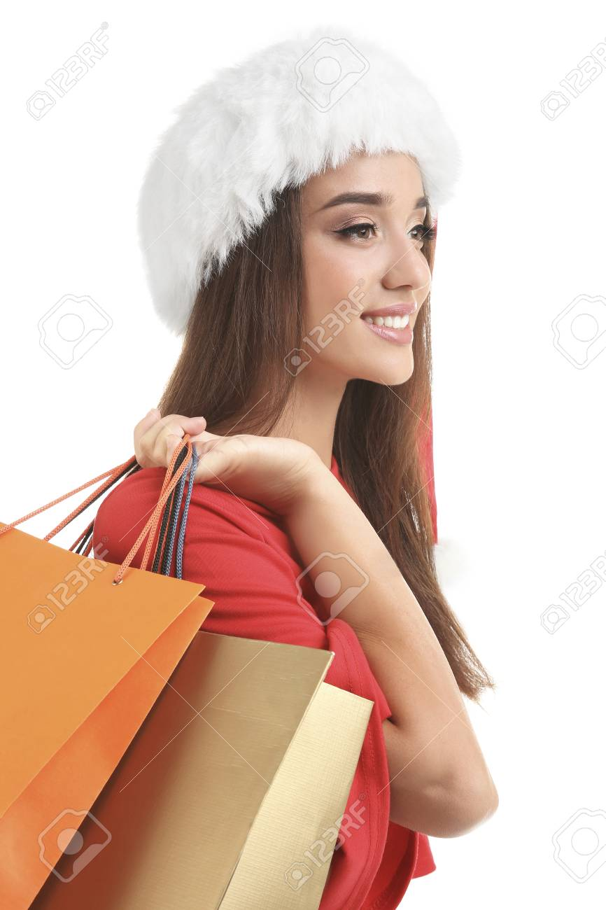 16dc2c90deb48 Stock Photo - Young woman in Santa hat holding colorful shopping bags on  white background. Boxing day concept