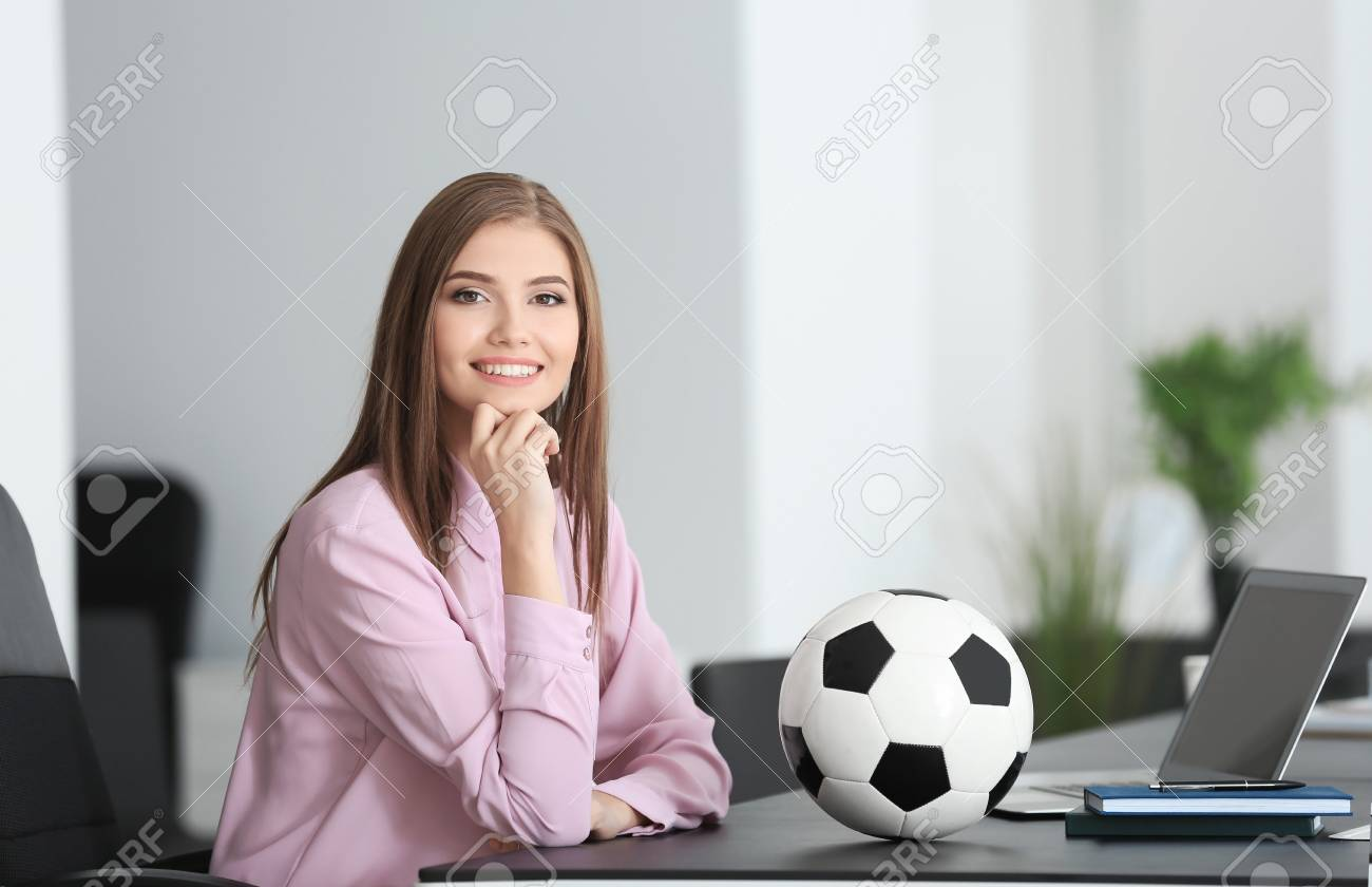 stock photo young beautiful woman with soccer ball in office