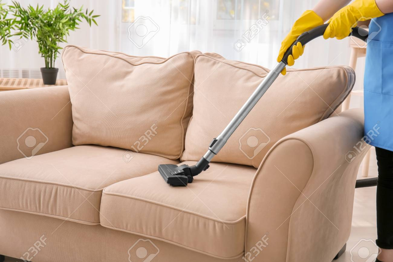 Stock Photo   Woman Cleaning Couch With Vacuum Cleaner At Home