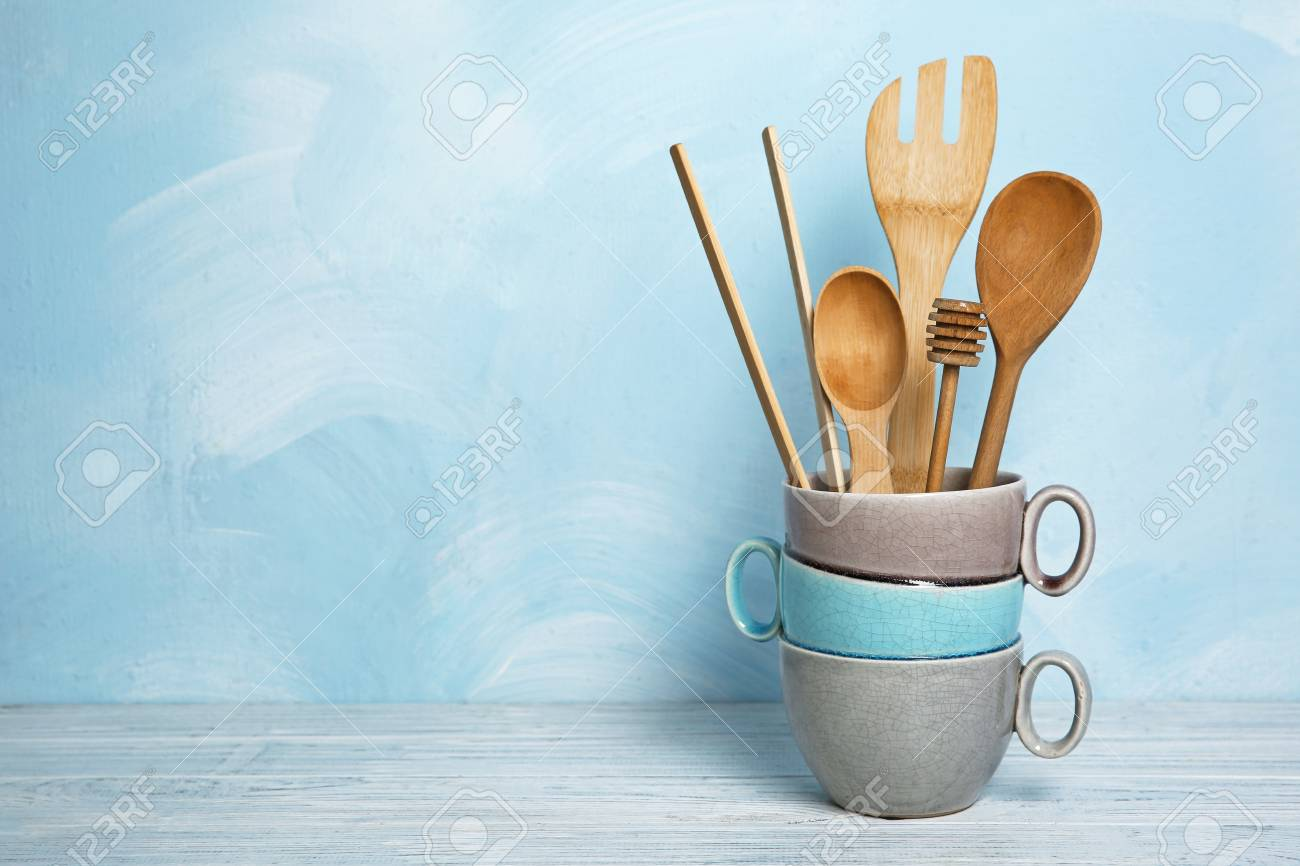 Wooden Kitchen Utensils In Vase On Table Against Blue Wall
