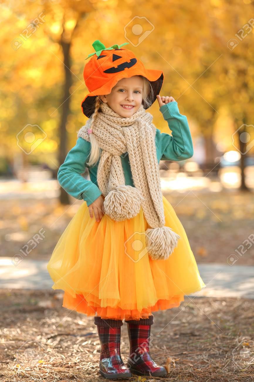 cute little girl wearing halloween costume in autumn park stock photo 99482859