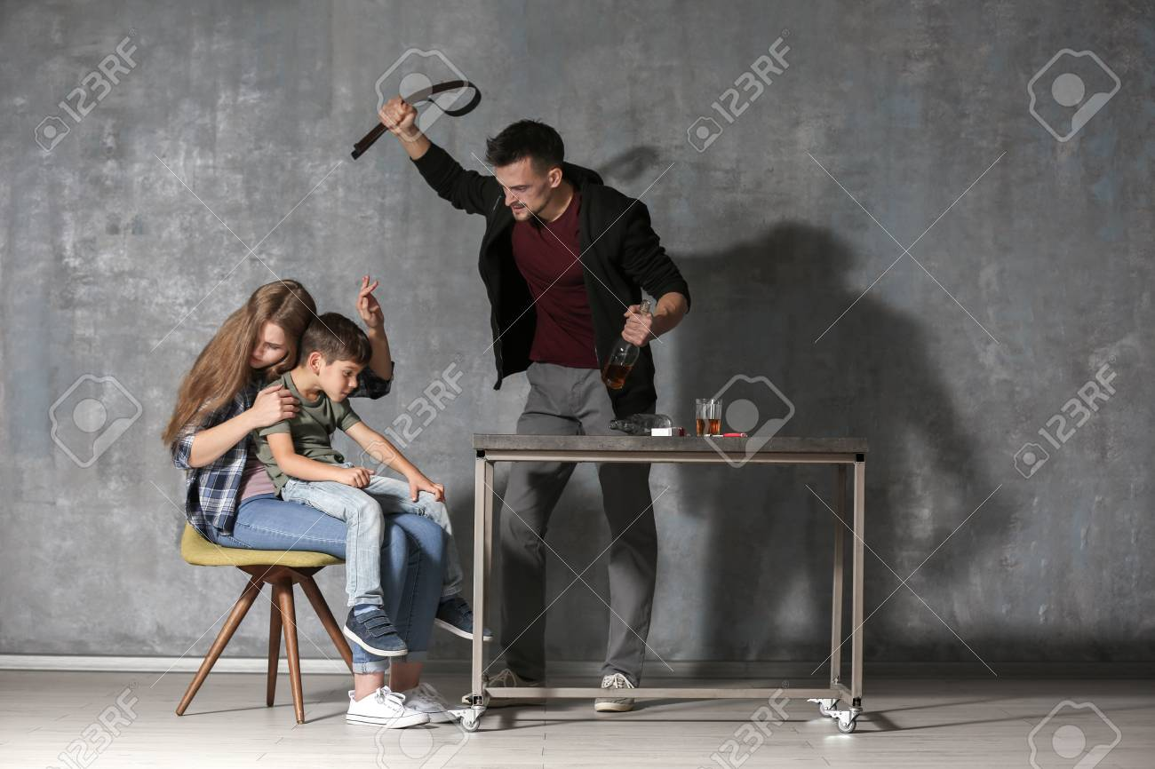 Drunk man threatening his wife and son against grey wall