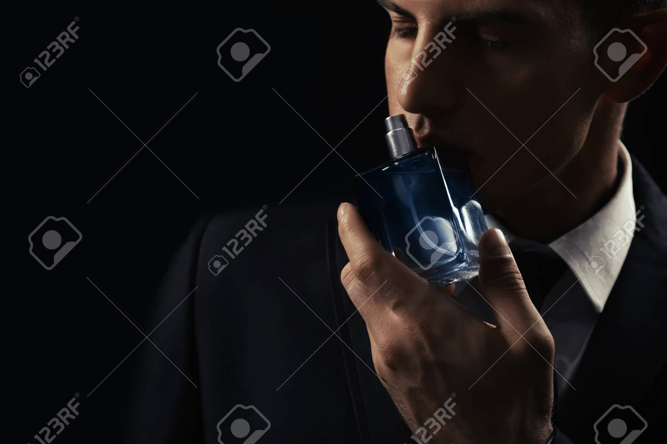 Handsome man with bottle of perfume on dark background, closeup - 99215081