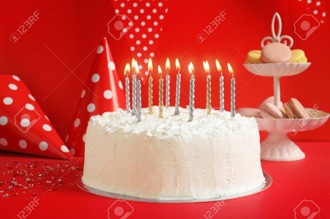 Birthday Cake With Candles On Table Against Red Wall Stock Photo