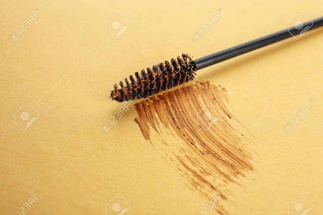 Brush With Smear Of Eyebrow Dye On Color Background Stock Photo