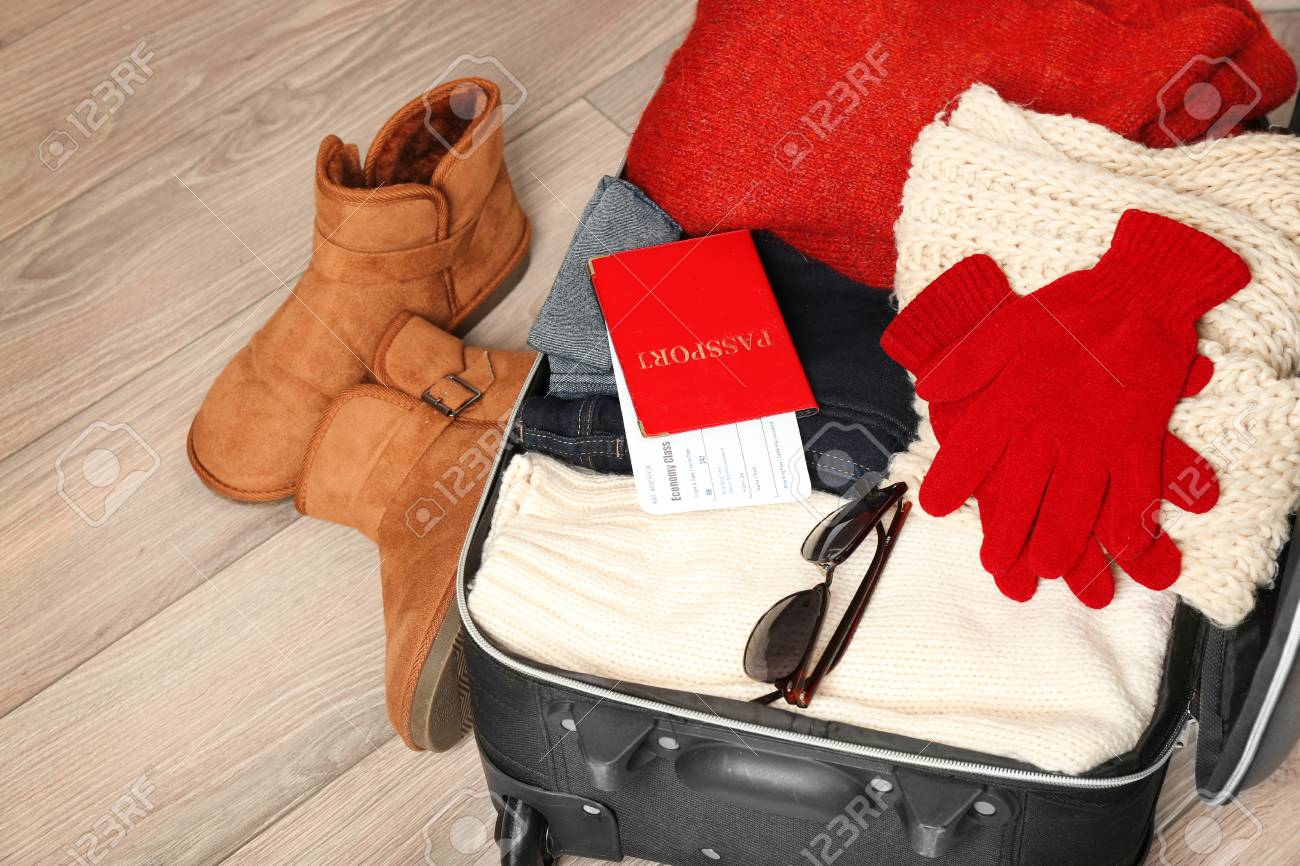 33d0ec14ad8 Open suitcase with warm clothes and documents on wooden floor. Winter  vacation concept Stock Photo