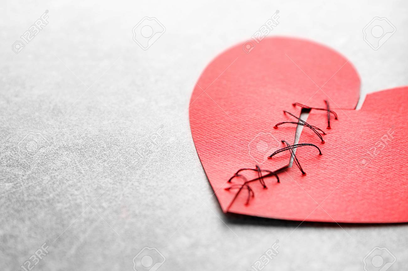 Paper heart cut in half and sewn back together on light background. Relationship problems - 99319568