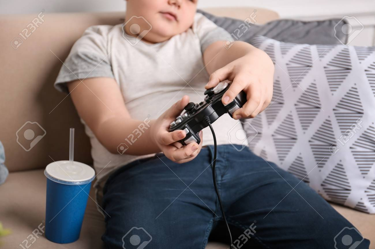 Overweight boy playing videogame indoors - 100409872