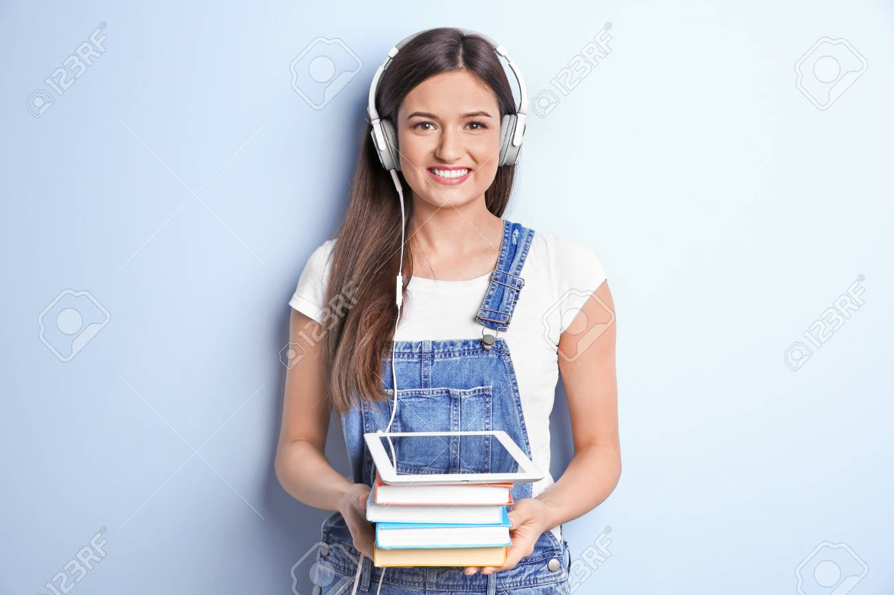 Woman listening to audiobook through headphones on color background - 100288019