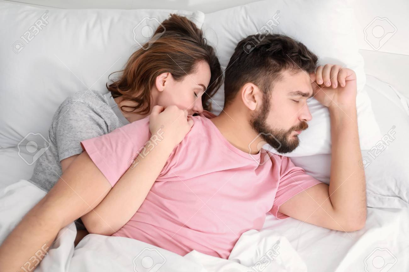 . Husband and wife sleeping in bed at home