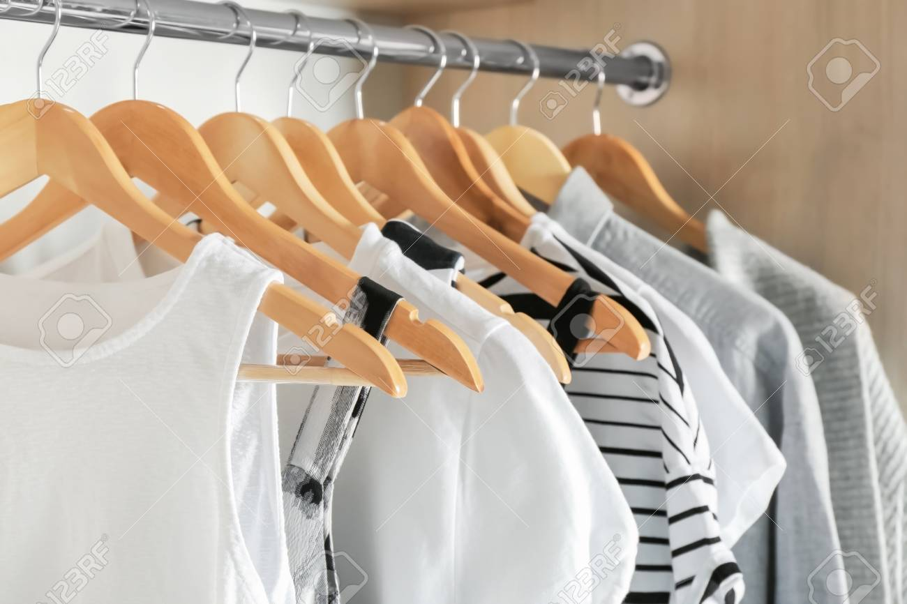 Hangers with different clothes in wardrobe closet - 99509276