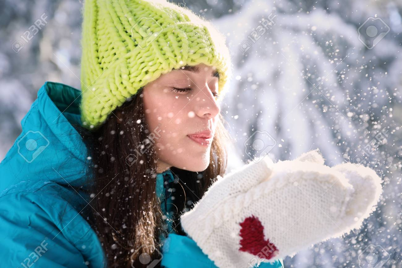 eb4dea5734ac0 Beautiful woman blowing snow on sunny frosty day. Winter vacation Stock  Photo - 99984030