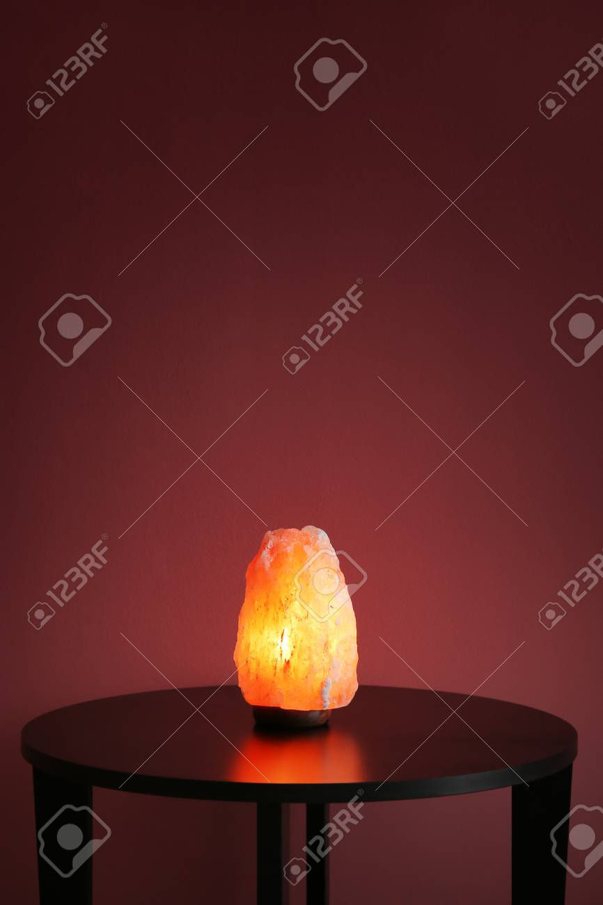 Himalayan Salt Lamp On Table Against Color Background Stock Photo
