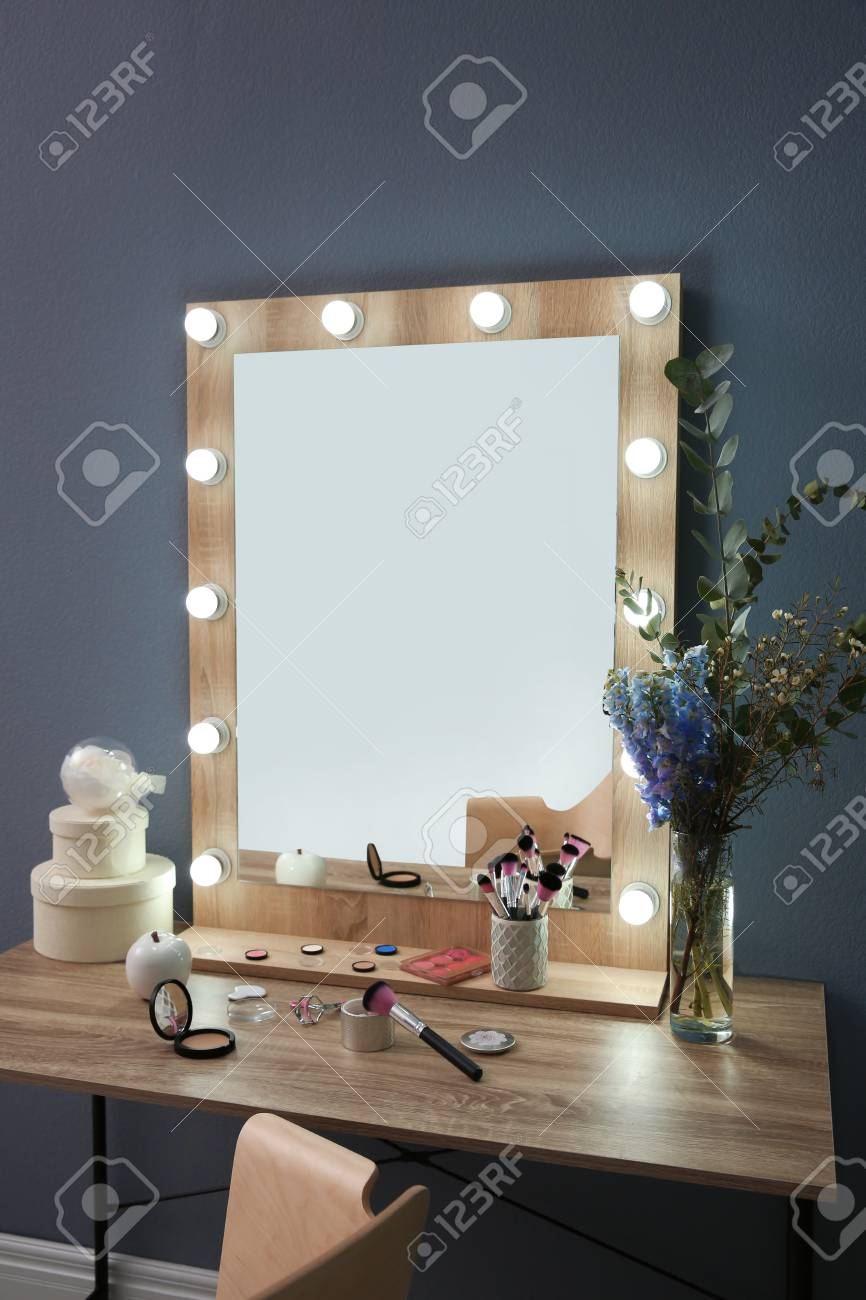 Table with beautiful mirror and cosmetics in modern makeup room - 105267291