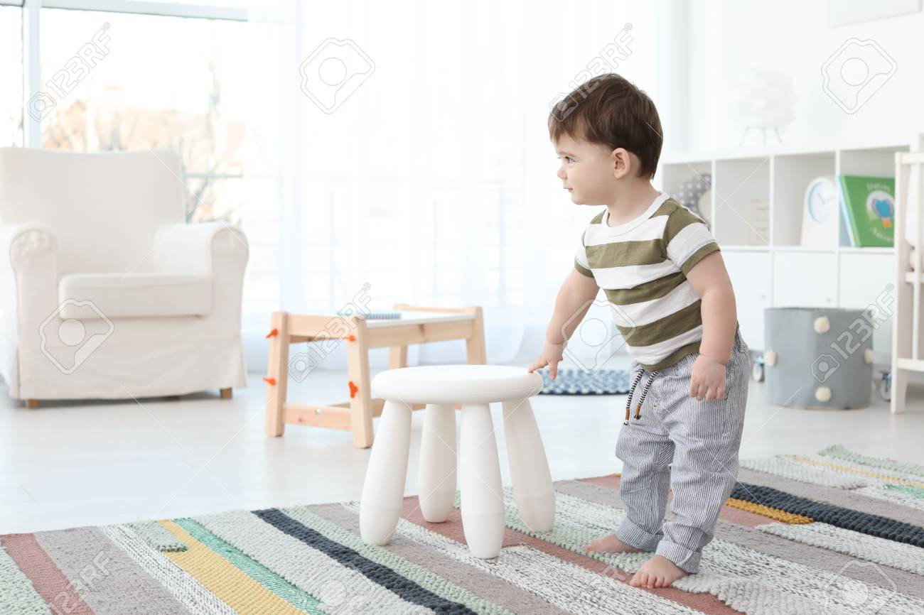 Cute Baby Holding On To Stool At Home Learning Walk Stock Photo Picture And Royalty Free Image 107093987