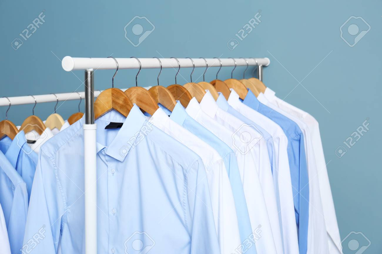 Racks With Clean Clothes After Dry-cleaning Against Color Background ...