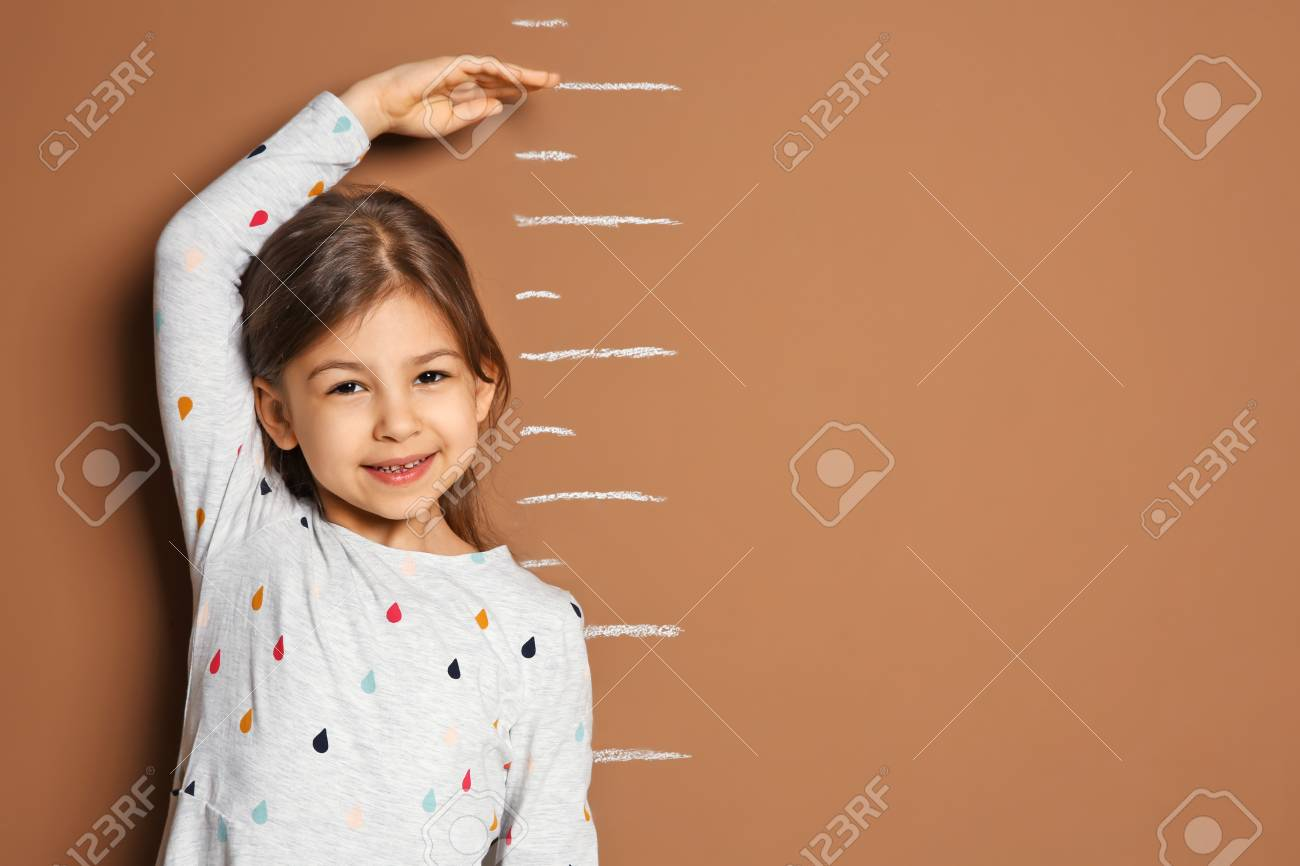 Little girl measuring her height on color background - 105412839