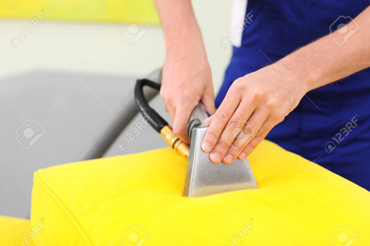Dry Cleaning Worker Removing Dirt From Sofa Cushion Indoors