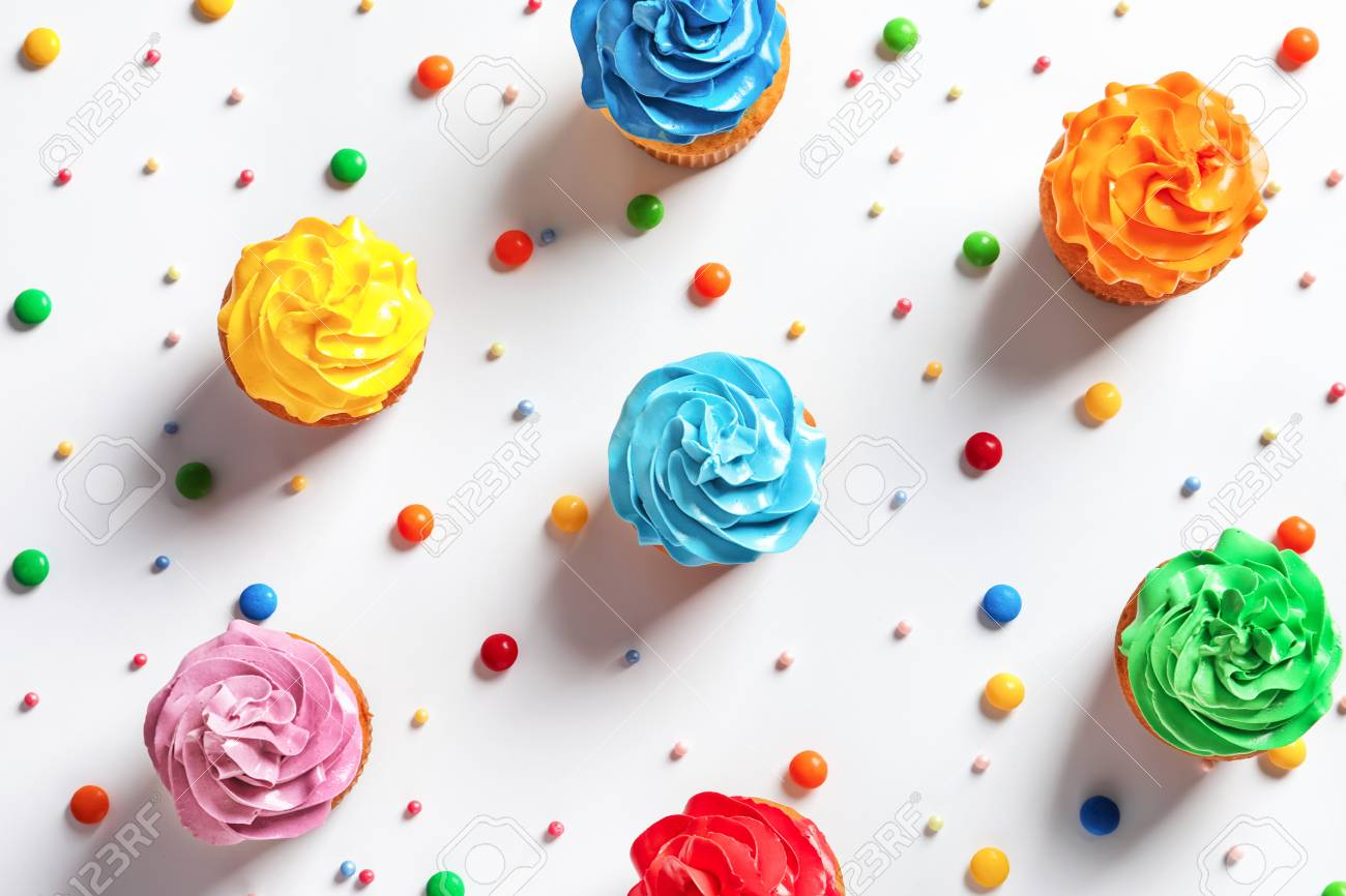 Flat Lay Composition With Colorful Birthday Cupcakes On Light Background Stock Photo