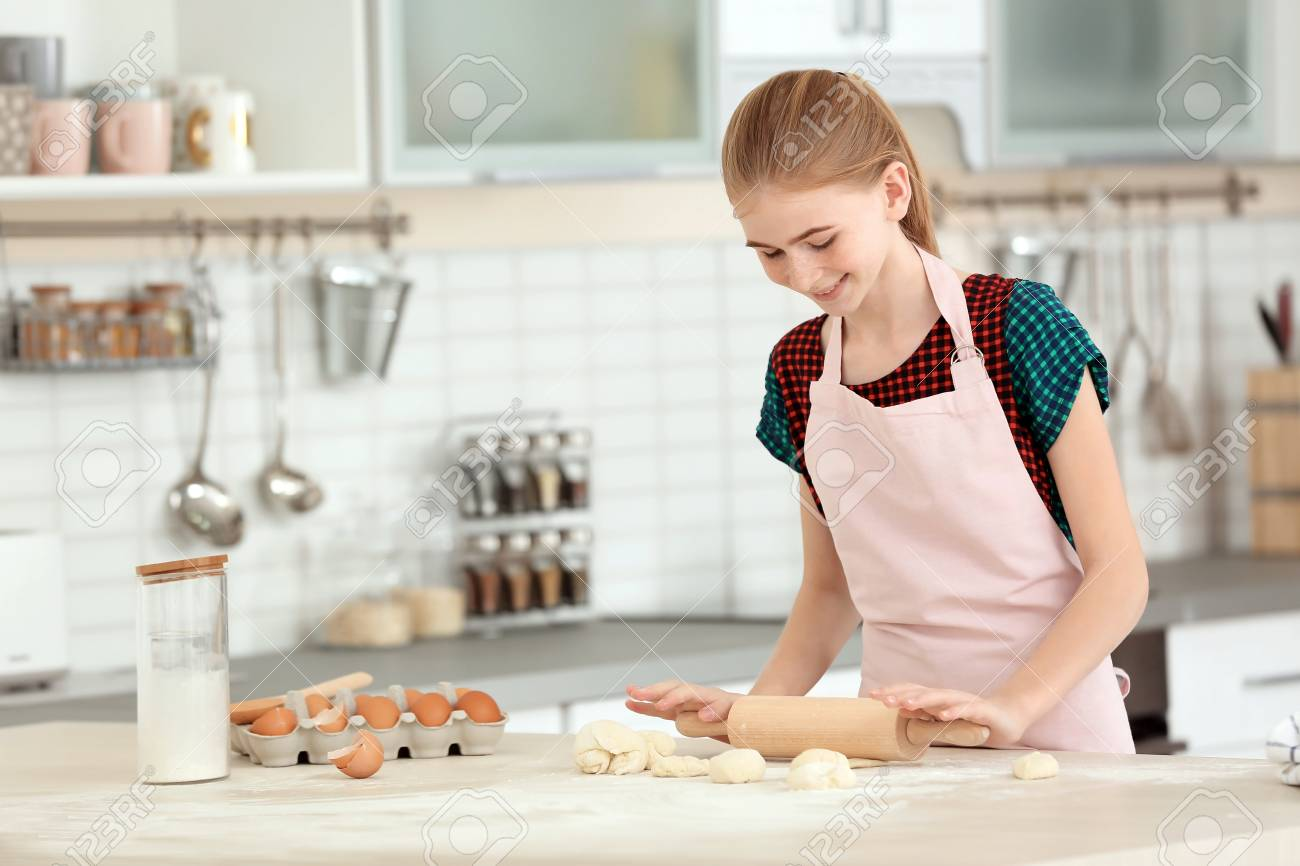 Teenage girl rolling dough on table in kitchen - 106508490