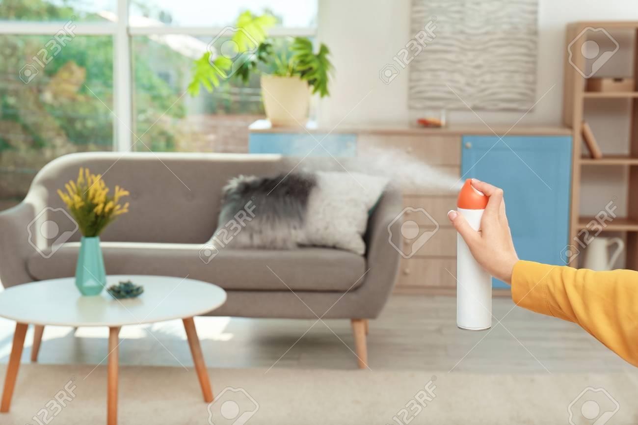 Woman spraying air freshener at home - 105946564