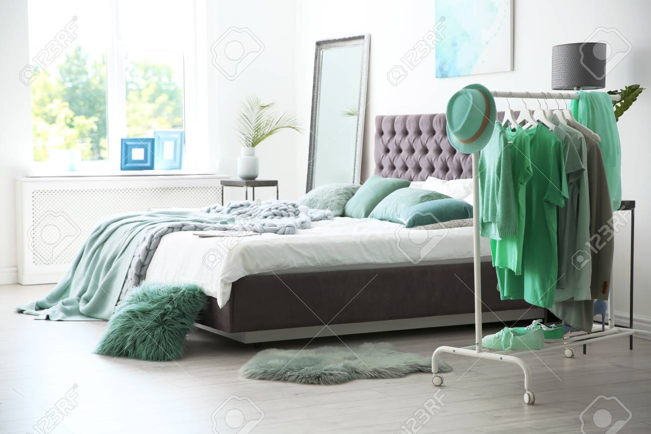 Stylish Bedroom Interior With Clothes Rack And Mint Decor Elements