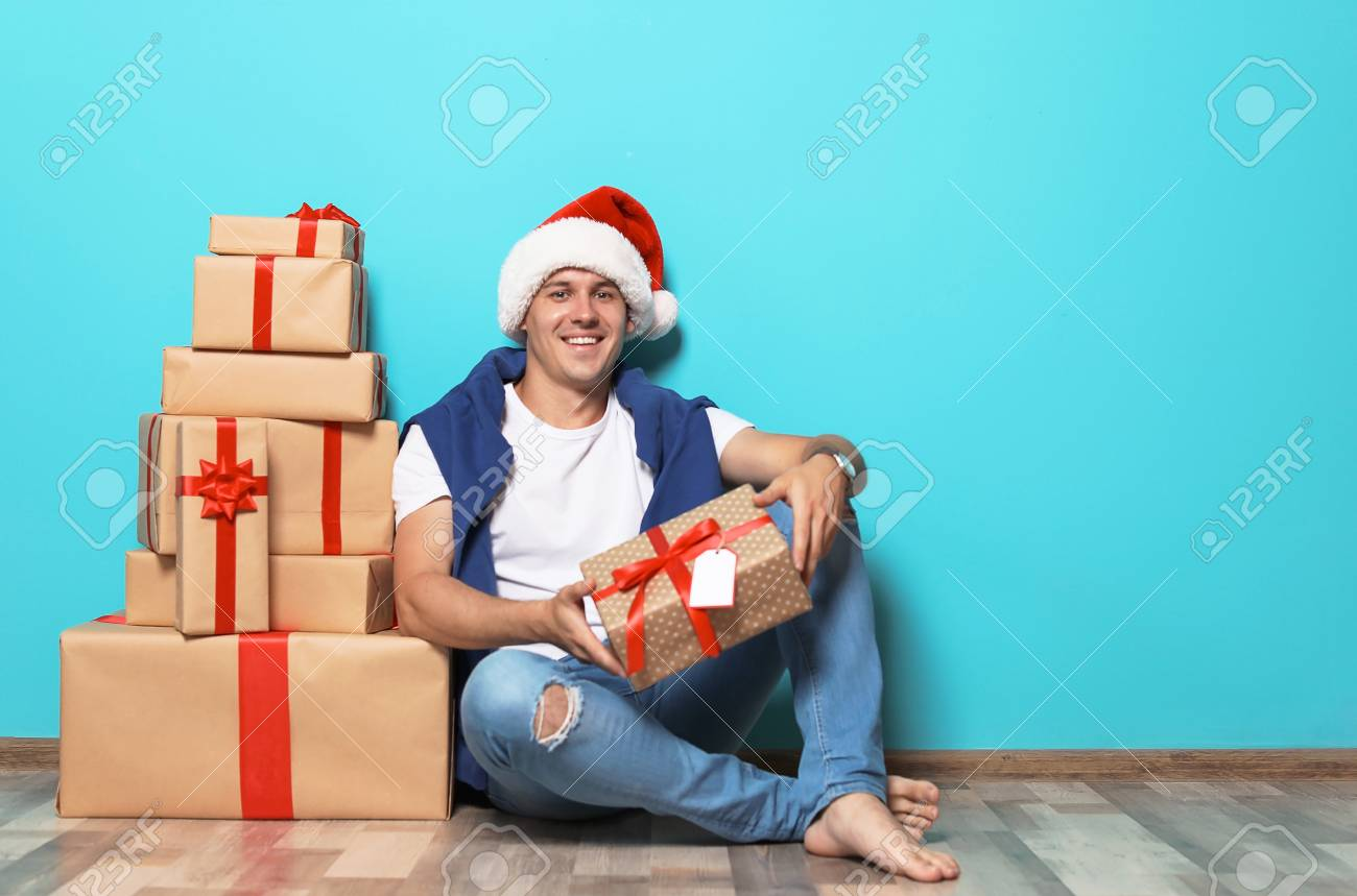 Stock Photo - Young man with Christmas gifts near color wall  sc 1 st  123RF.com & Young Man With Christmas Gifts Near Color Wall Stock Photo Picture ...