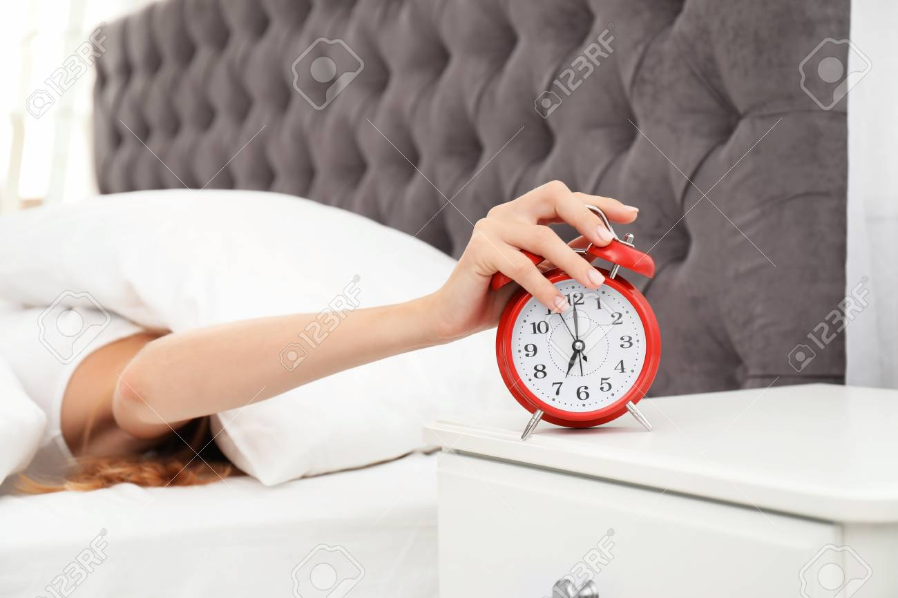 Woman Turning Off Alarm Clock In Bedroom Stock Photo, Picture And ...