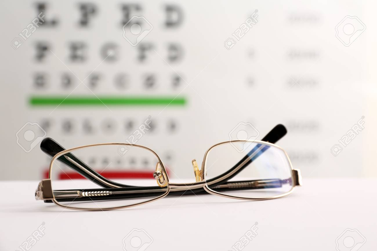 c10a7bb8d736 Glasses with corrective lenses on table against eye chart Stock Photo -  106506811