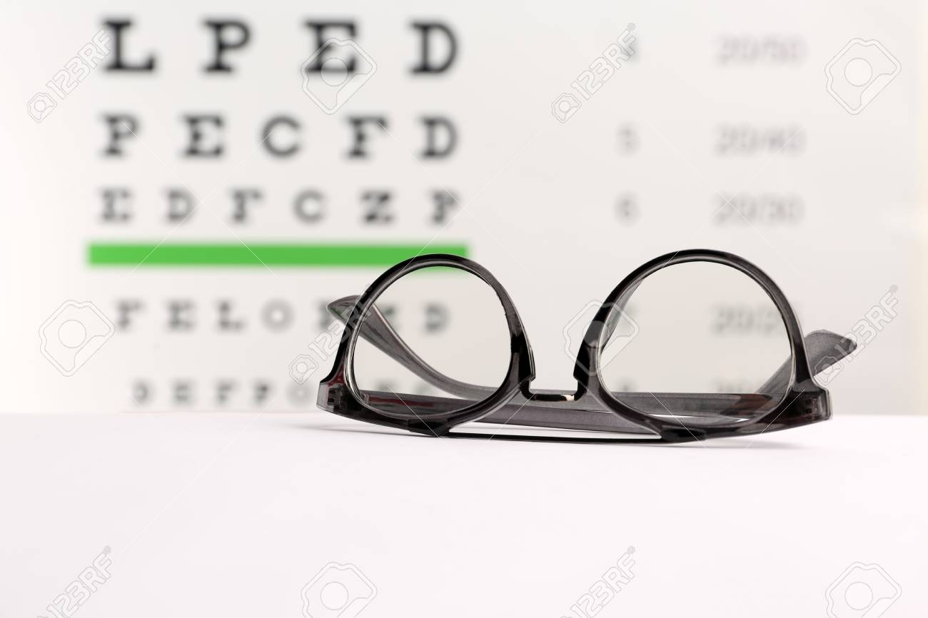 8e6c2124b436 Glasses with corrective lenses on table against eye chart Stock Photo -  106506930