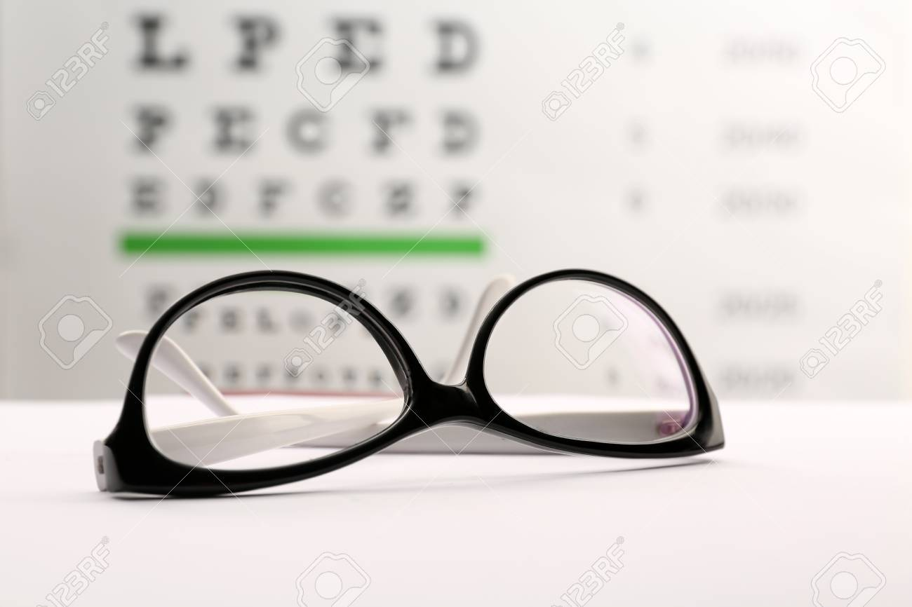 2afae835dd35 Glasses with corrective lenses on table against eye chart Stock Photo -  106506608