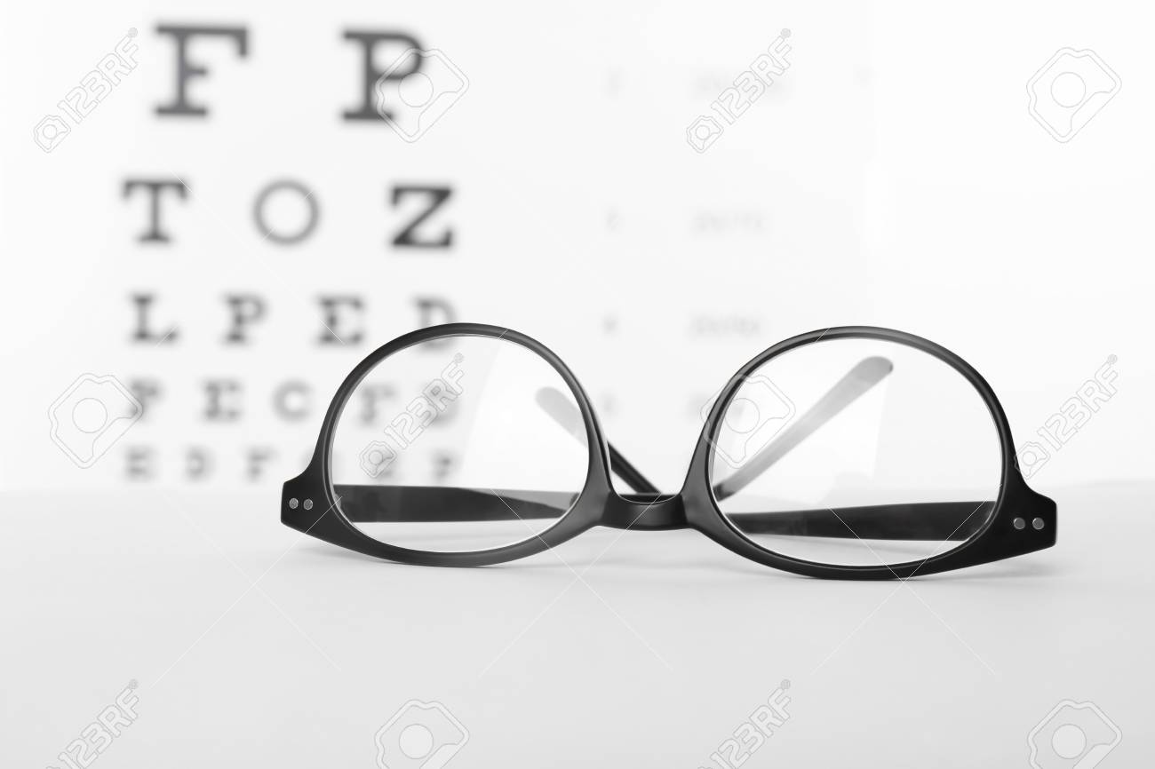 10a865d89c13 Glasses with corrective lenses on table against eye chart Stock Photo -  106548847
