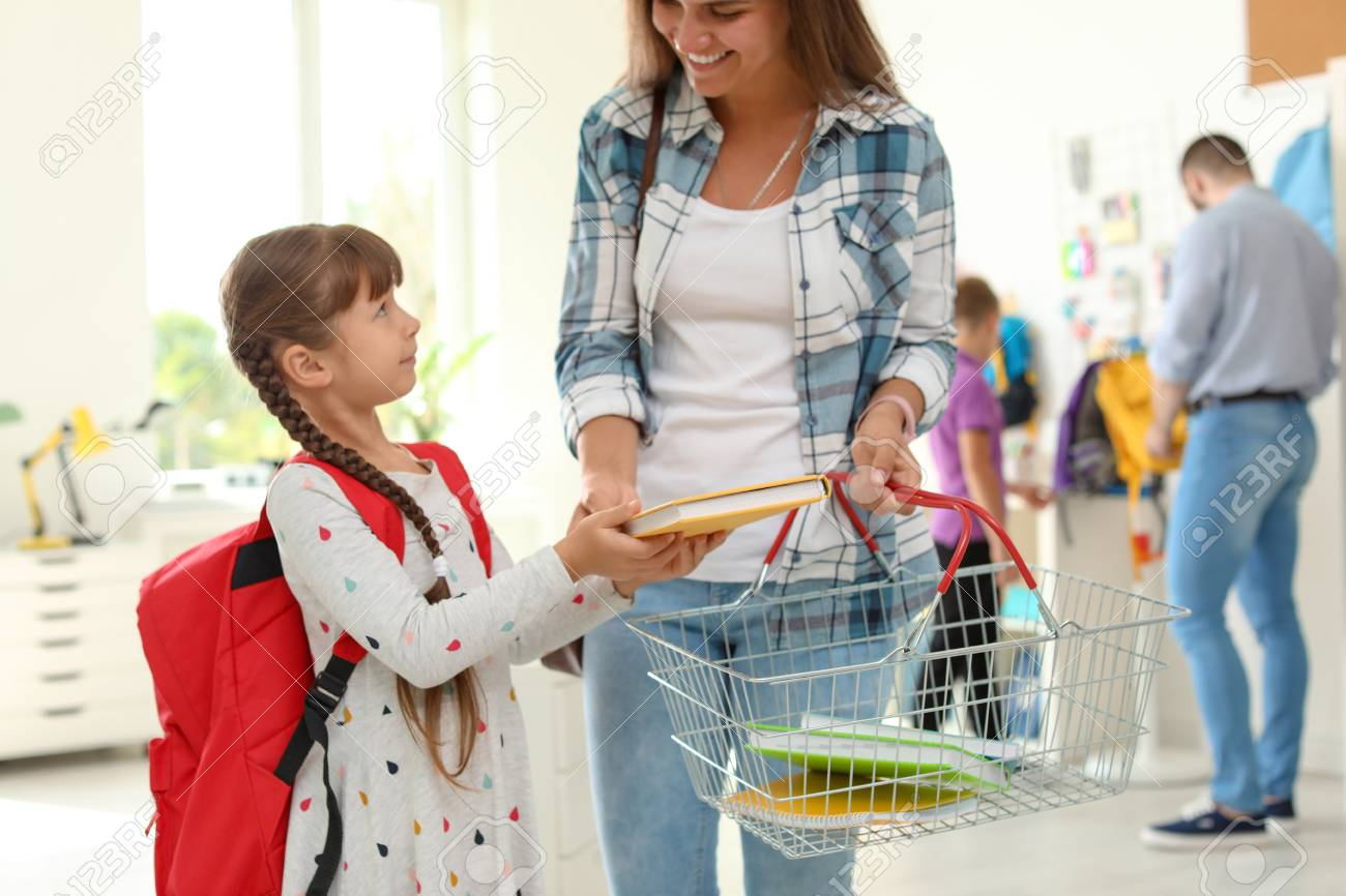Little girl choosing school supplies with mother in stationery shop - 107857579