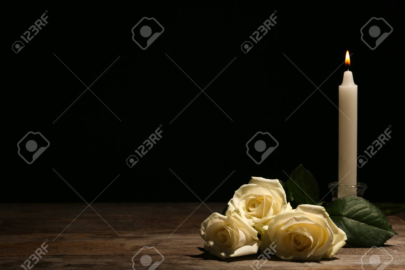 Beautiful white roses and candle on table against black background. Funeral symbol - 107029900