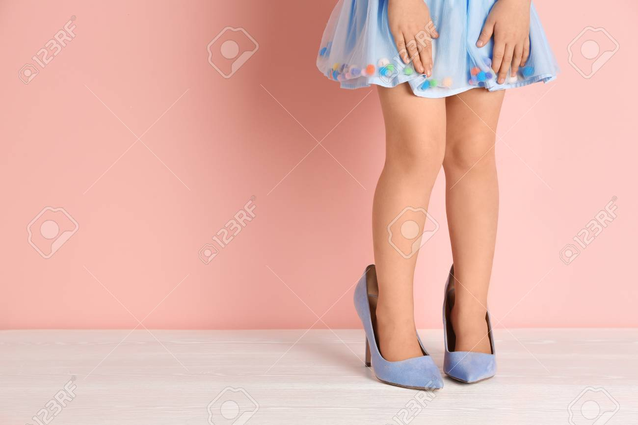 Little girl in oversized shoes near color wall with space for text, closeup on legs - 107423044