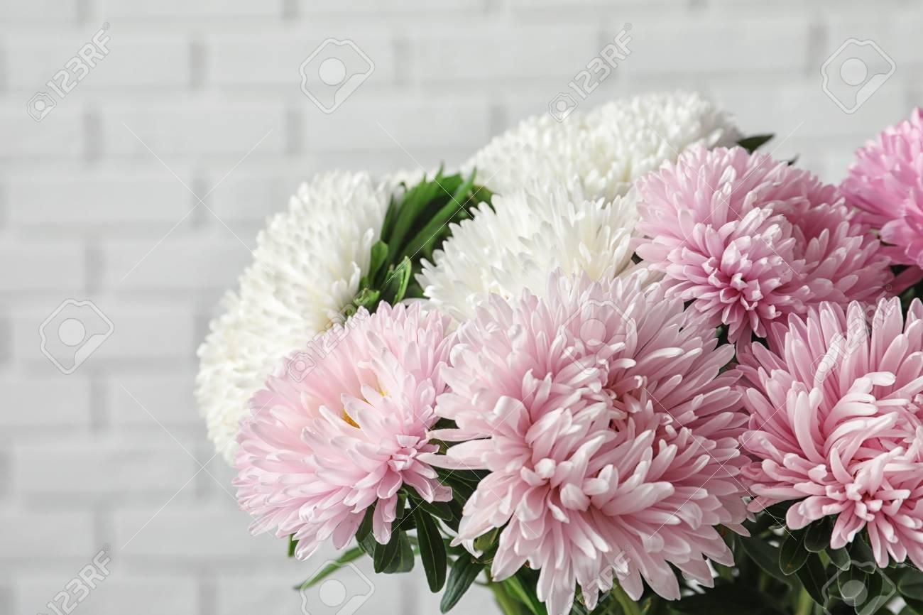 Beautiful Aster Flower Bouquet Near Brick Wall Closeup Stock Photo