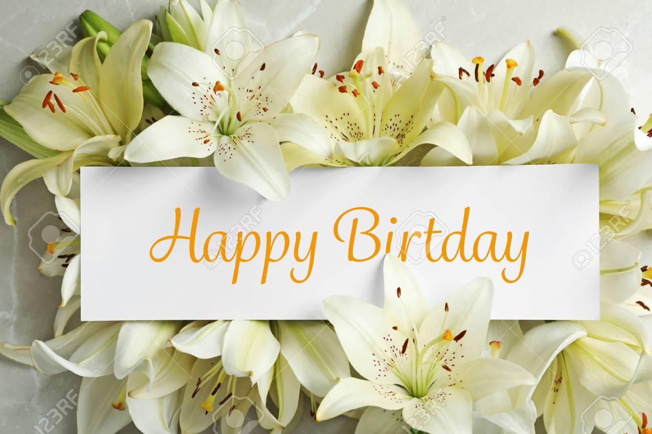 Composition Of Lily Flowers And Card With Greeting Happy Birthday